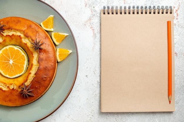 Bovenaanzicht lekkere ronde taart heerlijk dessert voor thee met stukjes sinaasappel op witte achtergrond fruittaart biscuit thee zoet dessert