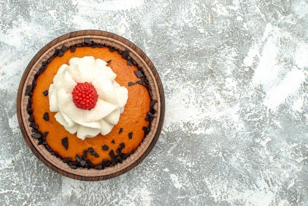 Bovenaanzicht lekkere rozijnencake met room op witte oppervlakte taart biscuit thee zoete cake suiker