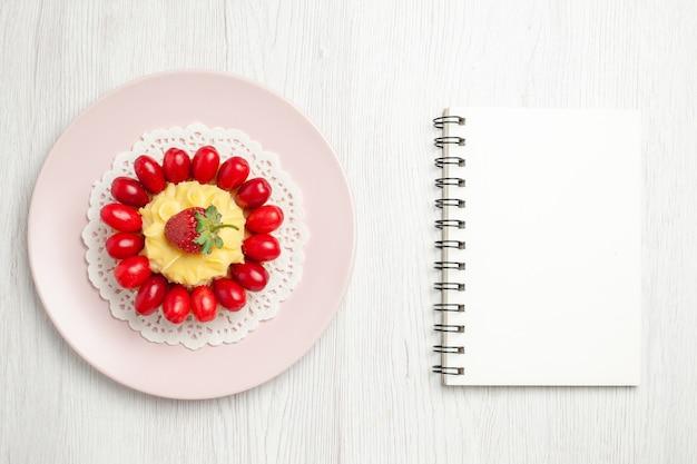 Bovenaanzicht lekkere slagroomtaart met kornoeljes op wit bureau