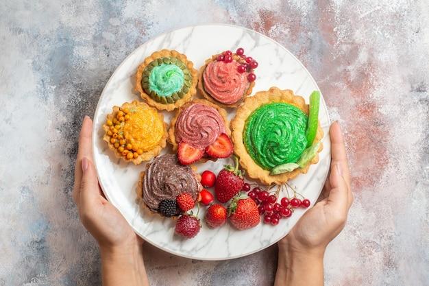 Bovenaanzicht lekkere slagroomtaarten met fruit op lichte tafel biscuit dessert zoete cake