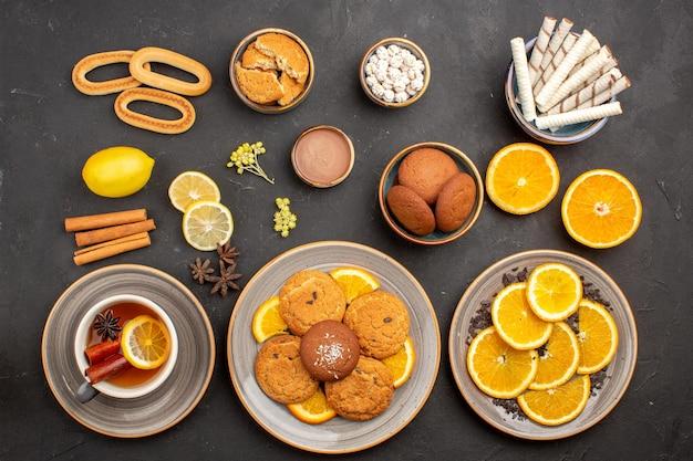 Bovenaanzicht lekkere suikerkoekjes met een kopje thee en sinaasappels op een donkere achtergrond, suikertheekoekje, zoet fruit