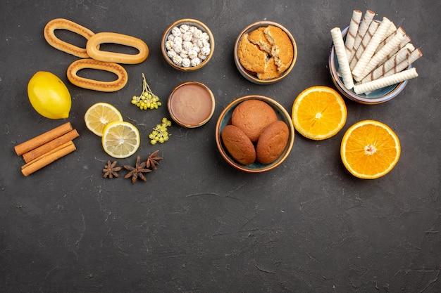 Bovenaanzicht lekkere suikerkoekjes met gesneden sinaasappels op de donkere achtergrond suikertheekoekje koekje zoet fruit