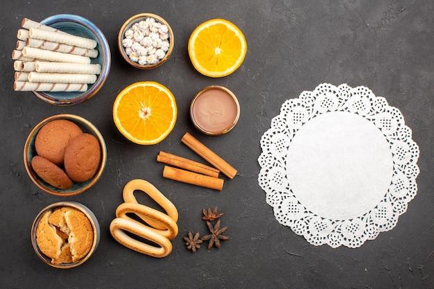 Bovenaanzicht lekkere suikerkoekjes met gesneden sinaasappels op donkere achtergrond, suikertheekoekje, zoet fruit