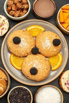 Bovenaanzicht lekkere suikerkoekjes met stukjes sinaasappel en cips op donkergrijze koekjeskoekjes, zoete theecake