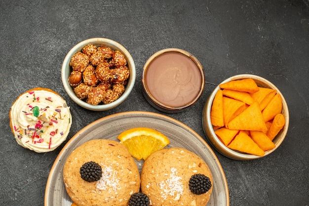 Bovenaanzicht lekkere suikerkoekjes met stukjes sinaasappel op donkere koekjeskoekjes, zoete theecake