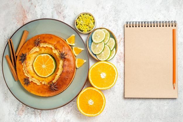 Bovenaanzicht lekkere taart heerlijk dessert voor thee met citroen en sinaasappel op de witte achtergrond fruitcake taart theekoekje zoet dessert