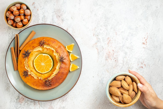 Bovenaanzicht lekkere taart heerlijk dessert voor thee met stukjes sinaasappel op witte achtergrond fruitcake taart theekoekje zoet dessert