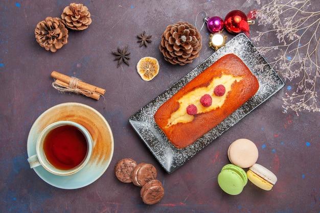Bovenaanzicht lekkere taart lang gevormd met kopje thee op donkere ondergrond cake suiker koekjes taart zoete biscuit thee
