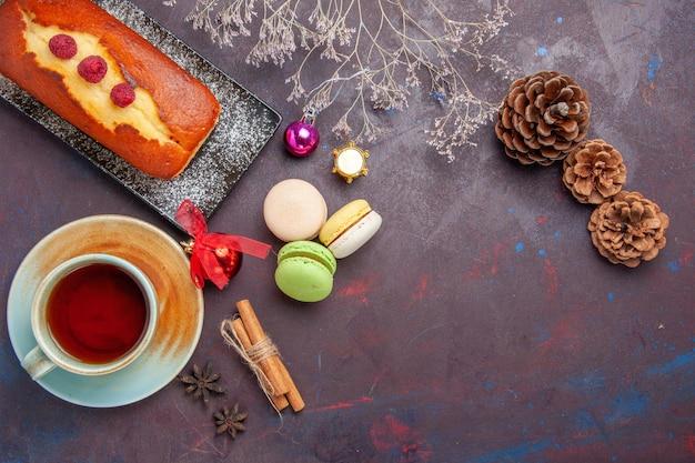 Bovenaanzicht lekkere taart met kopje thee op donkere oppervlakte cake suiker koekjes taart zoete biscuit thee