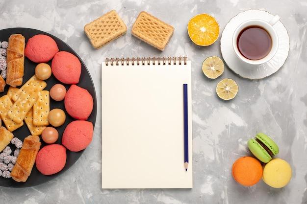Bovenaanzicht lekkere taarten met bagels macarons en kopje thee op grijs wit oppervlak