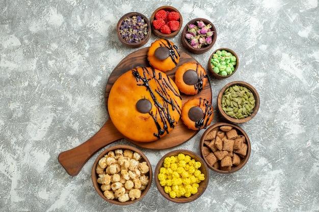 Bovenaanzicht lekkere taarten met chocoladesuikerglazuur en snoepjes op witte oppervlaktecake cacaokoekjestaart dessert zoet koekje
