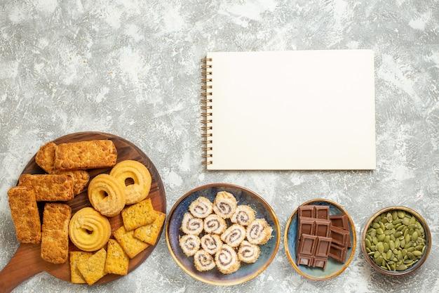 Bovenaanzicht lekkere taarten met snoepjes en koekjes op lichte witte achtergrond
