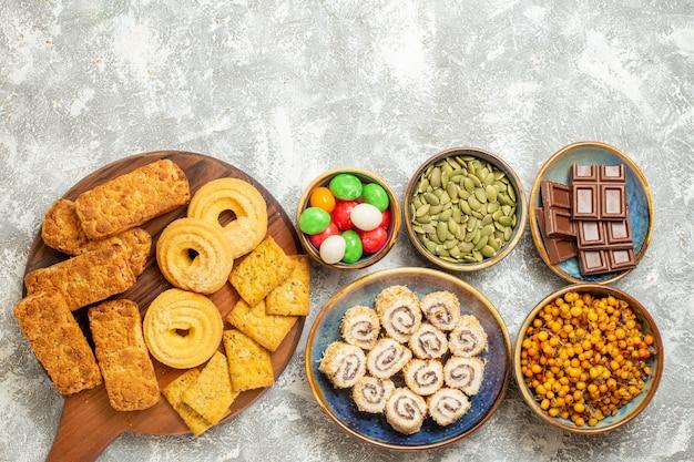 Bovenaanzicht lekkere taarten met snoepjes en koekjes op witte achtergrond