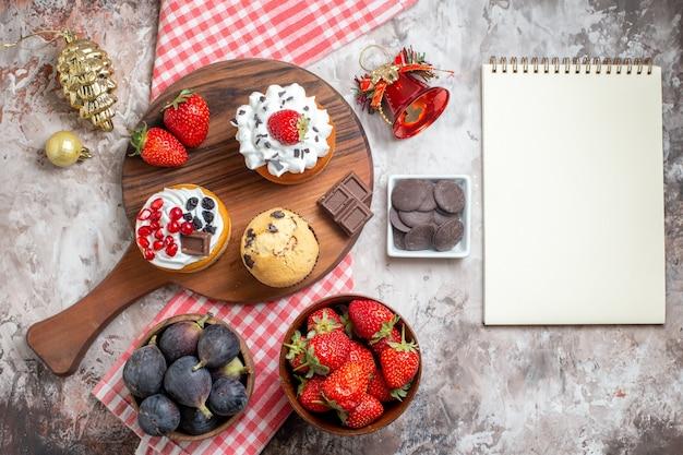 Bovenaanzicht lekkere taarten met vers fruit op lichte achtergrond