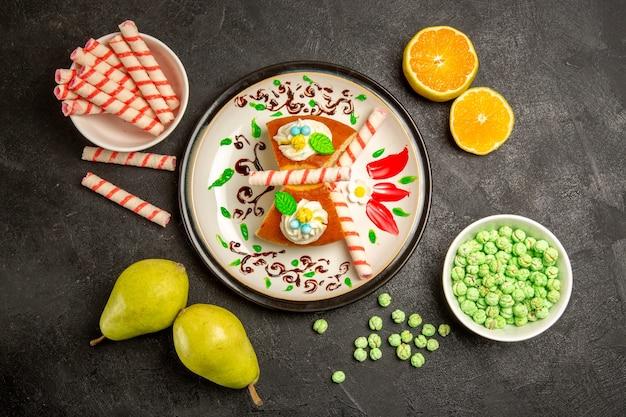 Bovenaanzicht lekkere taartplakken met snoep en fruit op grijs