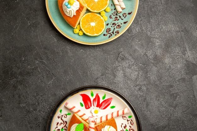 Bovenaanzicht lekkere taartplakken met vers gesneden mandarijnen op grijs