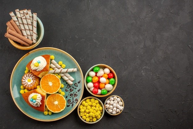 Bovenaanzicht lekkere taartplakken met verse mandarijnen en snoepjes in het donker