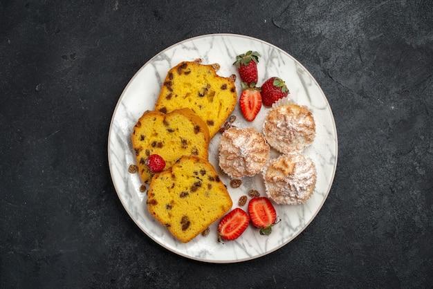 Bovenaanzicht lekkere taartschijfjes met verse rode aardbeien op donkergrijs oppervlak