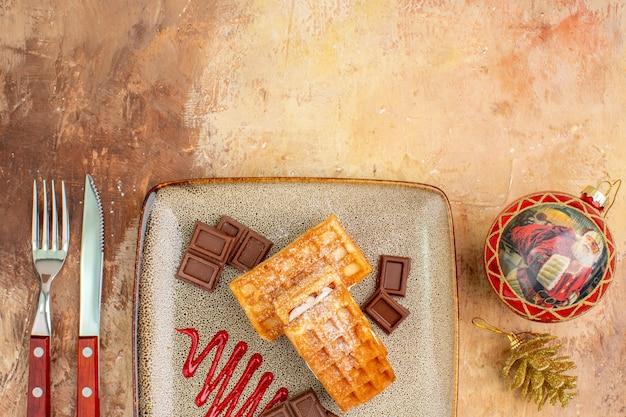 Bovenaanzicht lekkere wafelkoekjes met chocoladerepen op bruin bureau