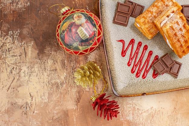 Bovenaanzicht lekkere wafelkoekjes met chocoladerepen op de bruine achtergrond