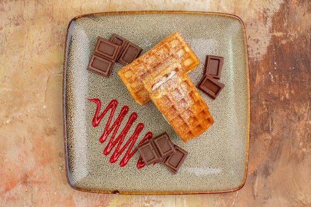 Bovenaanzicht lekkere wafelkoekjes met chocoladerepen op de bruine achtergrond Gratis Foto