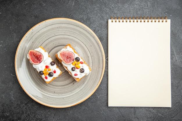 Bovenaanzicht lekkere wafelkoekjes met fruit op de donkere achtergrond