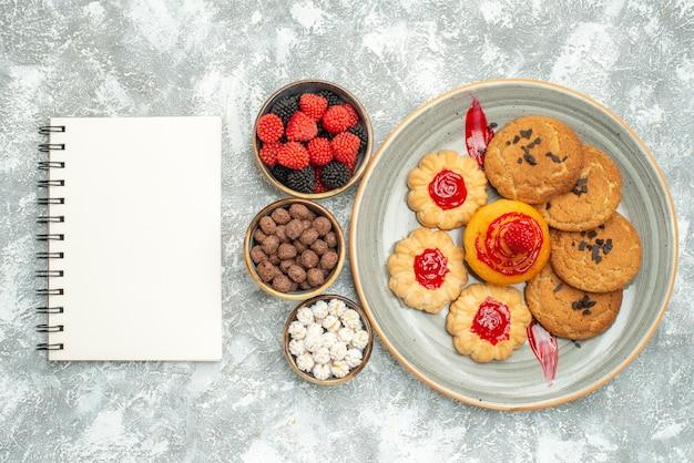 Bovenaanzicht lekkere zand koekjes met koekjes en snoepjes op wit