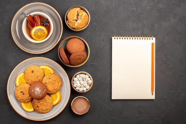 Bovenaanzicht lekkere zandkoekjes met gesneden sinaasappels en kopje thee op donkere achtergrond, fruit, citruskoekjes, zoete cakekoekjes