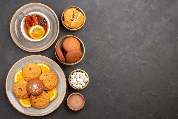 Bovenaanzicht lekkere zandkoekjes met gesneden sinaasappels en kopje thee op een donkere achtergrond, fruit, citruskoekje, zoete cakekoekje