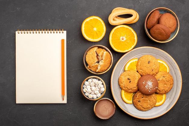 Bovenaanzicht lekkere zandkoekjes met gesneden sinaasappels op de donkere achtergrond, fruit, citruskoekje, zoete cakekoekje