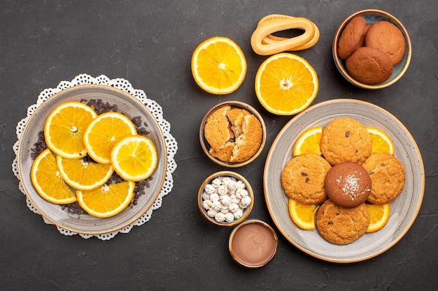 Bovenaanzicht lekkere zandkoekjes met gesneden sinaasappels op donkere achtergrondvruchten, citruskoekje, zoete cakekoekje