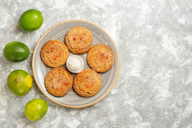 Bovenaanzicht lekkere zandkoekjes met groene citroenen op witte achtergrond Gratis Foto
