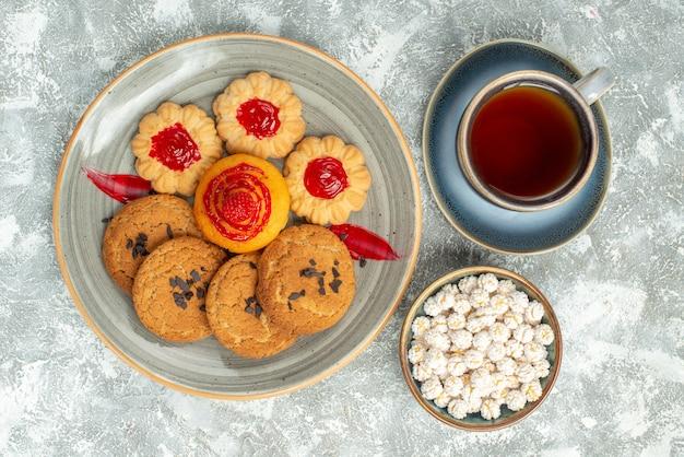 Bovenaanzicht lekkere zandkoekjes met koekjes en kopje thee op wit