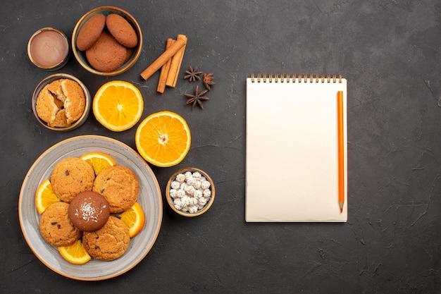 Bovenaanzicht lekkere zandkoekjes met vers gesneden sinaasappels op donkere achtergrond, fruitkoekjes, zoete koekjes, suiker, citruskleur
