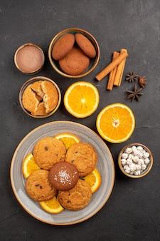 Bovenaanzicht lekkere zandkoekjes met vers gesneden sinaasappels op een donkere achtergrond, fruitkoekje, zoet koekje, citrussuiker