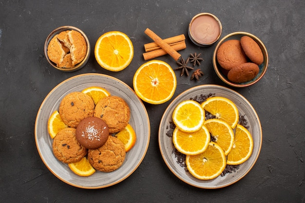 Bovenaanzicht lekkere zandkoekjes met vers gesneden sinaasappels op een donkere achtergrond, fruitkoekje, zoete koek, suiker, citruskleur