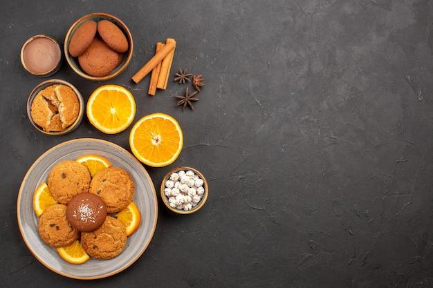 Bovenaanzicht lekkere zandkoekjes met vers gesneden sinaasappels op een donkere achtergrond, fruitkoekje, zoete koekjes, suiker, citruskleur