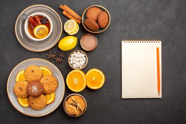Bovenaanzicht lekkere zandkoekjes met verse sinaasappels en kopje thee op donkere achtergrond, fruitkoekje, zoet koekje, citrussuiker