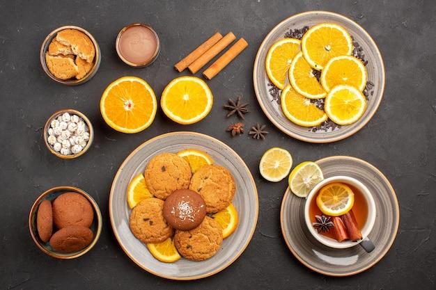 Bovenaanzicht lekkere zandkoekjes met verse sinaasappels en kopje thee op een donkere achtergrond, fruitkoekje, zoet koekje, citrussuiker