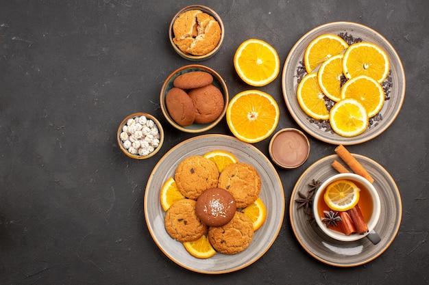 Bovenaanzicht lekkere zandkoekjes met verse sinaasappels en kopje thee op een donkere achtergrond, fruitkoekje, zoet koekje, citrussuiker Gratis Foto