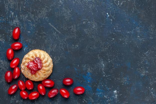 Bovenaanzicht lekkere zoete cake met rode kornoeljes op de donkergrijze achtergrond fruit bes kleur cake biscuit foto zoet