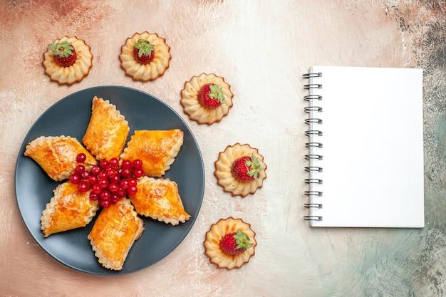 Bovenaanzicht lekkere zoete gebakjes, fruit en koekjes op wit taartgebak zoet