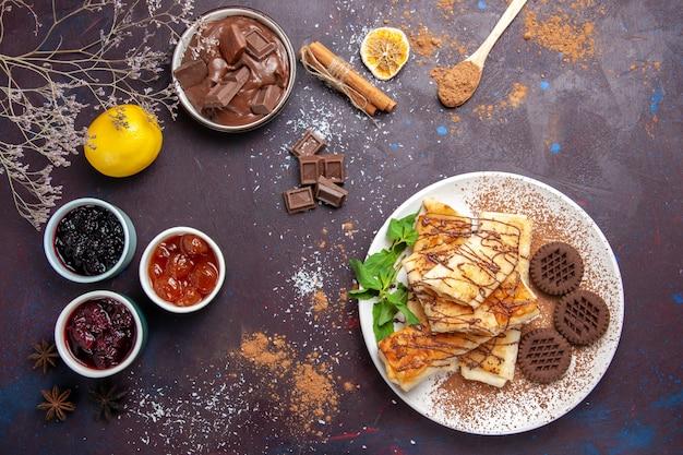 Bovenaanzicht lekkere zoete gebakjes met koekjes en jam op donkere achtergrond koekjeskoekje suiker thee zoete cake