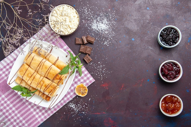 Bovenaanzicht lekkere zoete gebakjes met kwark en jam op donkere bureaukoekjes koekjes suiker thee zoete cake