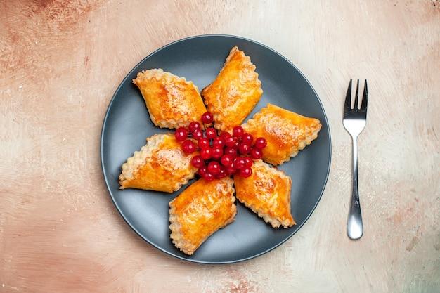 Bovenaanzicht lekkere zoete gebakjes met rode bessen op wit taartgebak zoet