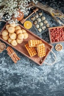 Bovenaanzicht lekkere zoete koekjes met kleine cakes en noten op lichtgrijze achtergrondkleur, zoete taartkoekje, bakkoekje, notensuiker