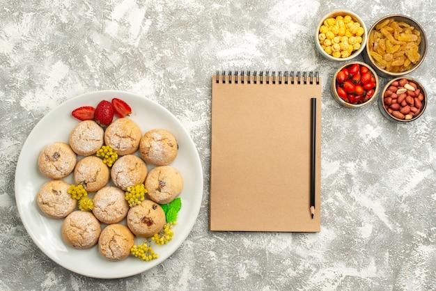 Bovenaanzicht lekkere zoete koekjes met rozijnen op witte achtergrond candy cookie biscuit zoete thee suiker