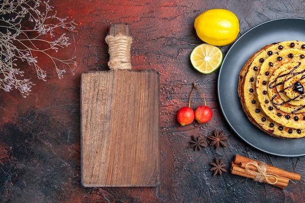 Bovenaanzicht lekkere zoete pannenkoeken met citroen op donkere ondergrond