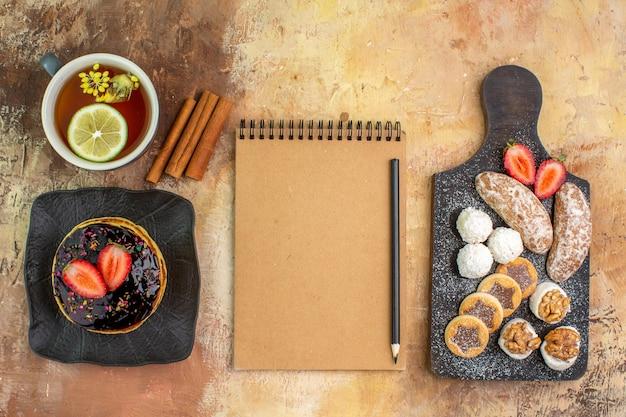 Bovenaanzicht lekkere zoete pannenkoeken met kopje thee en snoep op licht bureau