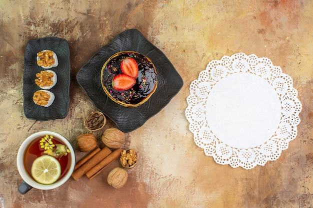 Bovenaanzicht lekkere zoete pannenkoeken met kopje thee op houten bureau